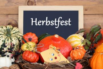 Image of a chalkboard behind pumpkins that says Herbstfest.
