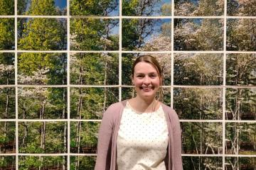 Picture of Dr. Jacobs in front of an artwork depicting trees.